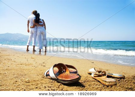 Young attractive couple at the beach (focused front view)