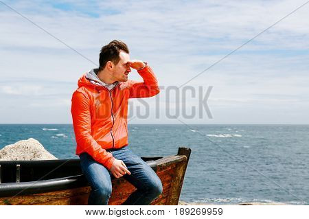 Young man in jeans and red jacket sits on the edge of a boat by the sea, looking at the distance, hand on forehead
