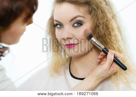 Make up and beauty. Makeup artist applying with brush powder rouge on female check