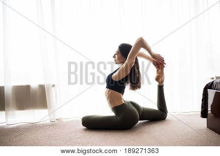 Young Attractive Smiling Woman Practicing Yoga, Sitting In One Legged King Pigeon Exercise, Eka Pada