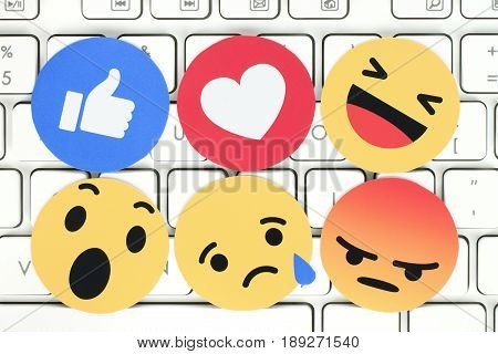 Kiev Ukraine - February 07 2017: Facebook like button 6 Empathetic Emoji Reactions printed on paper and placed on computer keyboard. Facebook is a well-known social networking service
