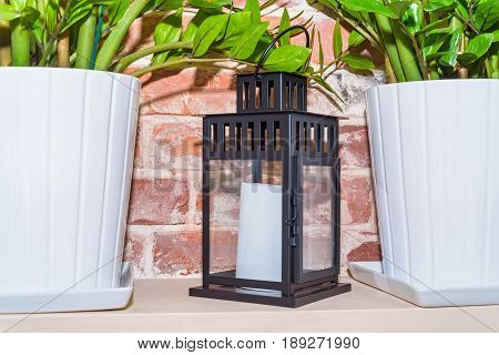 Close up of black lantern with white unlit candle inside used for interior decoration