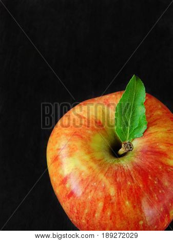 Close-up of a red apple on a black background. Empty place for a text