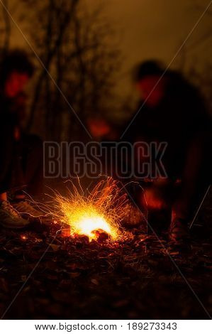 Close up picture of group of men sitting around speed fire trajectories taken with slow shutter