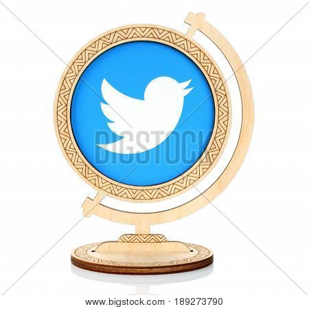 Kiev Ukraine - March 03 2017: Twitter paper logo placed in wooden globe on white background. Twitter is an online social networking service that enables users to send and read short messages