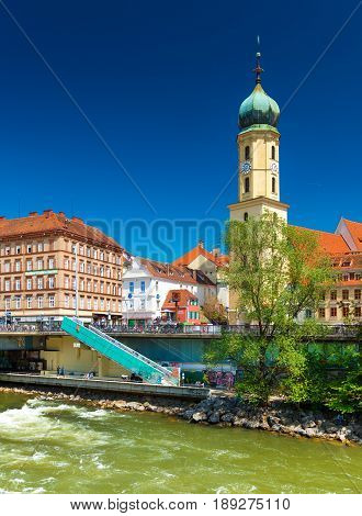 Graz - May 2017, Styria region Austria: View of the old city center. Franciscan Church, old historical buildings with orange roofs against the clear blue sky. Flowing river Mur