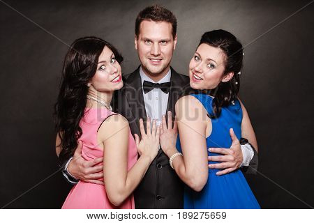 Love triangle or friendship. Portrait of smiling two women and one man wearing elegant clothes on black. Luxury party.