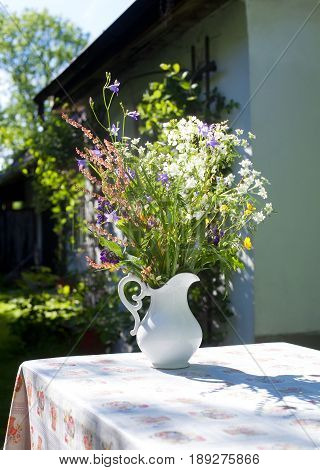 Jug of Wild Flowers on a Table Outside Country House.