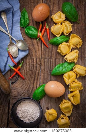 raw italian pasta tortellini on wooden board with basil