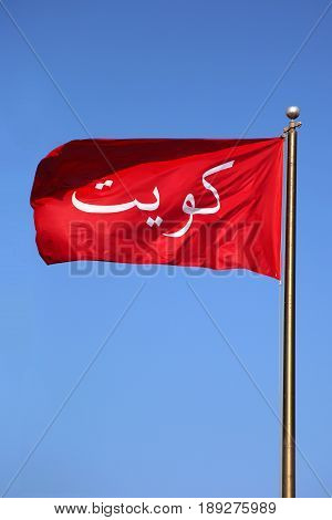 Waving Old Red Flag Of Kuwait On A Daytime Deep Blue Sky