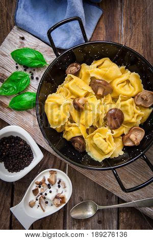 raw italian pasta tortellini on wooden board with japanese mushroom shiitake