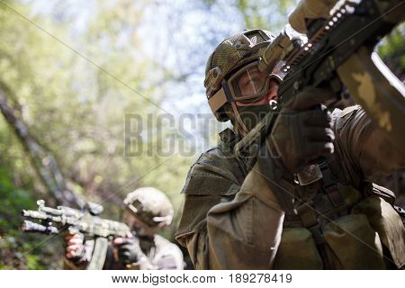 Group of officers on reconnaissance in woods during day