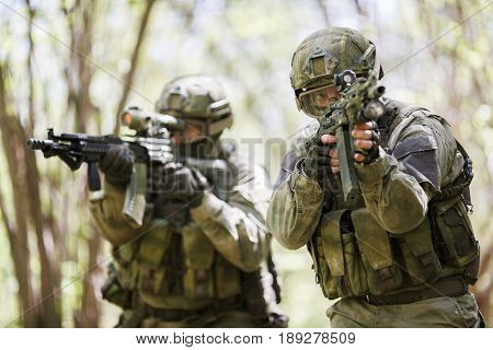 Military men with weapons on reconnaissance in forest