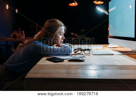 Side View Of Exhausted Businesswoman Looking At Computer Screen At Workplace