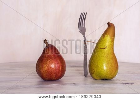 Red and yellow pear on the table. Pear with a fork. Still life with pears.
