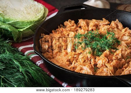 Delicious stewed cabbage in iron pan on dark rustic background with the ingredients for this dish. vegetarian food
