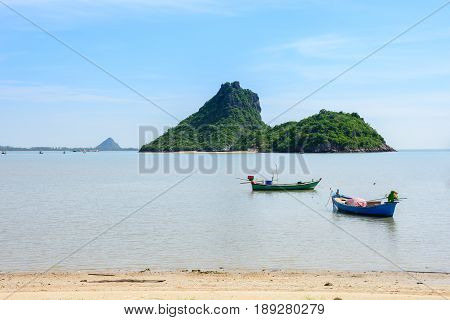 Beachfront scenery with fishing boats landing at Prachuap Khiri Khan Thailand.