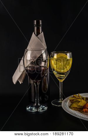 Open Bottle Of Wine With White Napkin, Large Glass Filled With Red Wine, Water With Lemon, White Pla