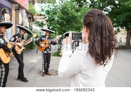 The girl makes selfie with Mexican musicians on the street
