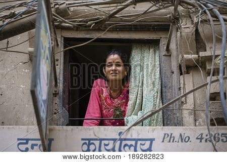 KATHMANDU NEPAL - SEPTEMBER 28 2016 : Nepalese woman looks out of a window to the street in Kathmandu Nepal