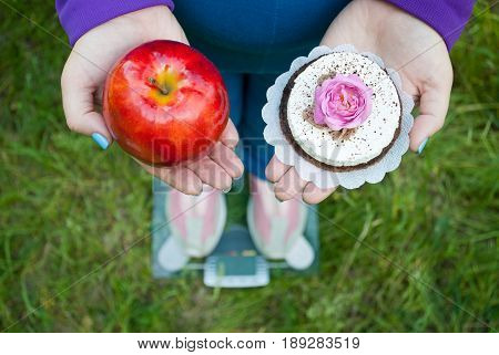 Fat woman wants to lose weight diet top view in blue suit stands on transparent glass scales in pink sneakers on green grass selects red big apple or round brown with white cake with rose of pink color holds them in hands with short blue nails on blurred