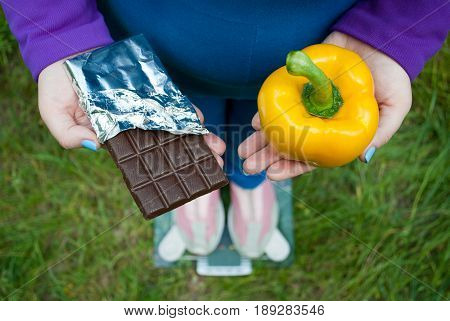 Fat woman wants to lose weight diet top view in blue suit stands on transparent glass scales in pink sneakers on green grass selects large yellow sweet Bulgarian pepper or chocolate bar in foil chocolate keeps them in hands with short blue nails on blurre