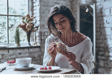 Enjoying fresh croissant. Attractive young woman enjoying fresh croissant while sitting at the table at home
