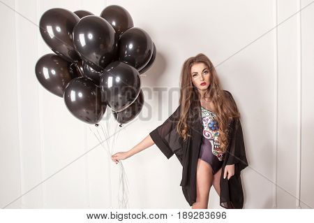 Beautiful young woman with perfect body and long hair posing on a white background with a lot of baloons. Woman wearing combination.