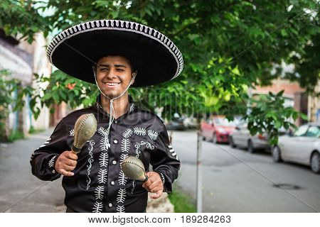 Mexican musician in traditional costume mariachi with maracas on the street