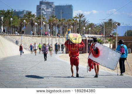 BARCELONA, SPAIN - MAY 2017: Beach lifeguard men are walking along the promenade of Barceloneta beach.
