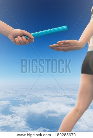 Digital composite of Relay runner and hand with baton against sky