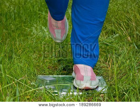 Sport athlete thick woman lose weight standing on scales legs left leg raised blue sports trousers knee-deep in pink sneakers glass transparent scales on green grass blurred background front view