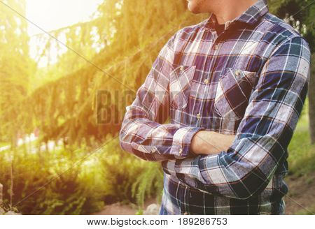 Man standing with arms crossed in park. Man waiting in park. Photo stock.