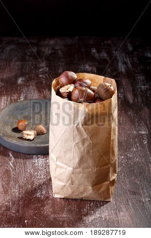 Roasted edible chestnuts in paper bag on dark wooden table.