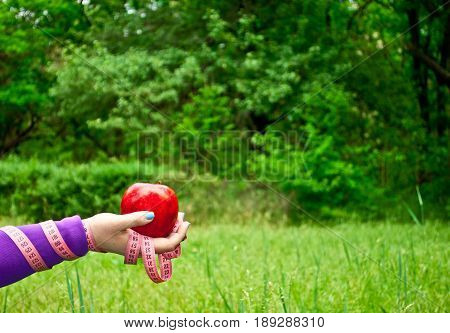 Lose weight fat woman close-up of the right hand holds a large red apple short nails blue on a background of green grass blurred background pink measuring tape wound on the hand side view