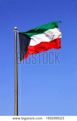 Waving National Flag Of Kuwait On A Blue Daytime Sky