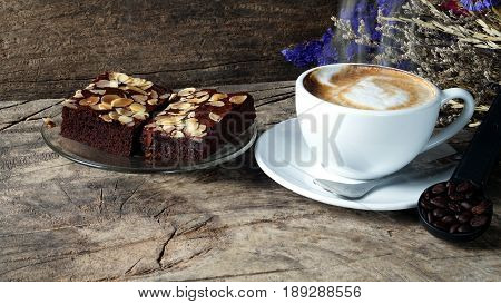 Cappuccino coffee and sweet chocolate brownies cake. A cup of latte, cappuccino or espresso coffee with milk put on a wood table with dark roasting coffee beans. Morning breakfast with coffee