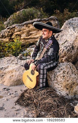Musician mariachi with guitar on the coast.