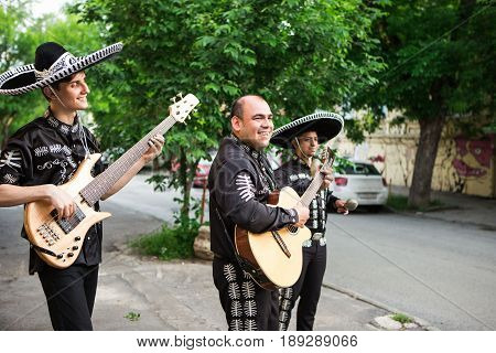 Mexican musicians in traditional costumes mariachi on the streets of the city