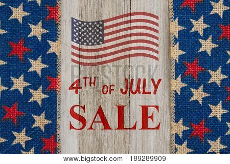 4th of July Sale text with USA red and blue stars burlap ribbon on weathered wood