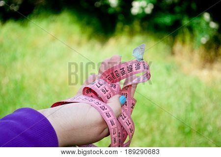 Fat woman wants to lose weight diet side view in purple suit on green grass holds in hands measuring tape pink color figures on her sits blue butterfly hand with short blue nails on blurry background lightness flit