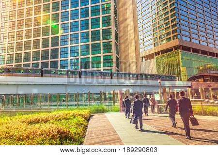 Tokyo, Japan - April 20, 2017:Tokyo urban businessmen commuter walking in Shiodome, an area with high skyscrapers in Shinbashi Financial District.Yurikamome monorail at Shiodome Station. Daylight shot