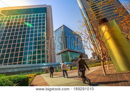 Tokyo, Japan - April 20, 2017: Tokyo urban businessmen commuter walking, Shiodome skyscrapers in Shinbashi Financial District, Minato Ward. Commuter Business District and corporate cityscape concept.