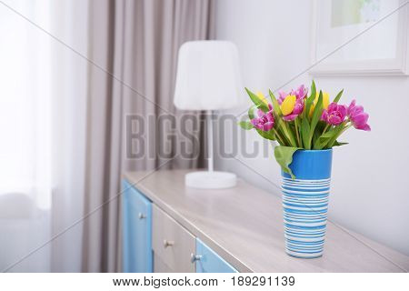 Vase with bouquet of beautiful tulips on chest of drawers