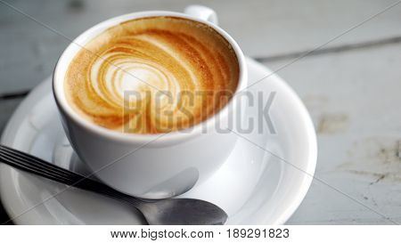 Hot cappuccino or latte art coffee. A cup of coffee on the wooden table. Morning breakfast with coffee. Latte art created by pouring steamed milk.