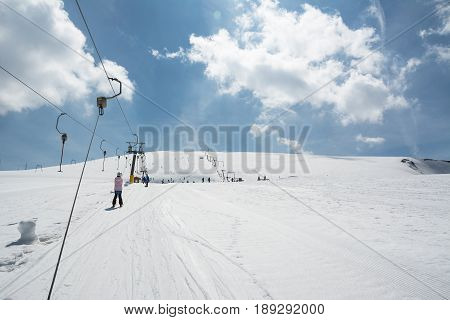 Beginner little girl with skis ascends with ski lift