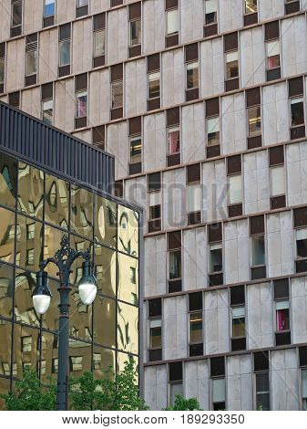 The windows in a tall building contrast with the wall of windows in a low building in which fascinating images of other buildings in downtown Detroit, Michigan are seen.