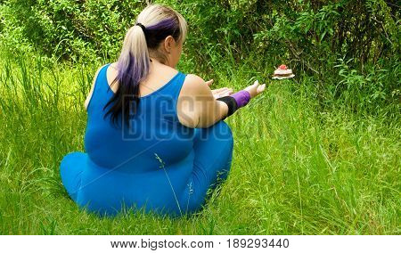 Fat woman wants to lose weight diet view from behind sits on grass image man figure in blue suit bush tree pulls his arms stretches to strive for flying floating cupcake levitation fly off trunk arrangement on the left purple black short nails blue on blu