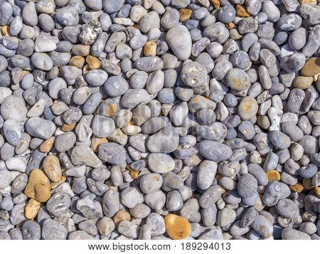 Background of smooth pebbles in different colors and sizes on the beach.