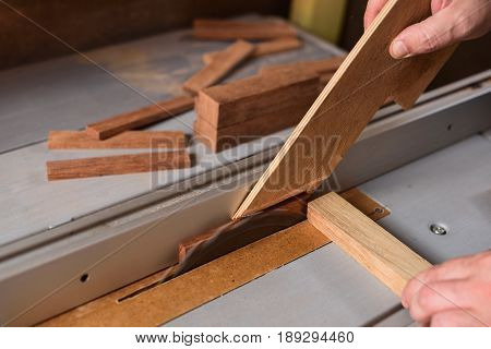 Carpenter sawing wood detail on circular saw hepling with stick for safety working